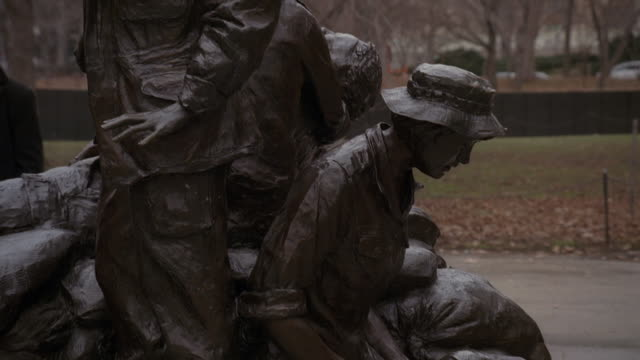 TU The Vietnam Women's Memorial statue with the Vietnam Veterans Memorial Wall beyond / Washington, D.C., United States