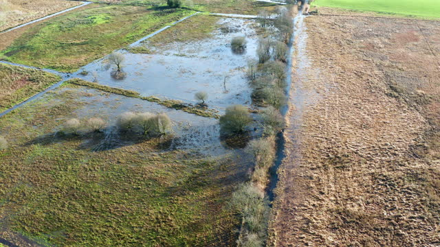 the view from a drone as it is flown over drainage ditches starting to overflow and flood onto farmland in south west scotland - weather stock videos & royalty-free footage