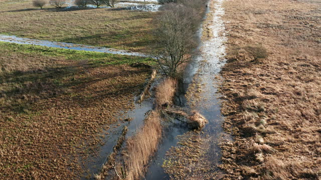 the view from a drone as it is flown over drainage ditches starting to overflow onto farmland in south west scotland - extreme weather stock videos & royalty-free footage