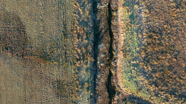 vídeos de stock e filmes b-roll de the view from a drone looking directly down on a drainage ditch in rural scotland - descuidado