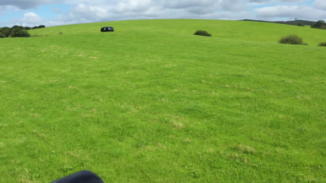 the view from a drone of bales of silage or hay wrapped in black plastic in a field in rural dumfries and galloway, south west scotland - johnfscott stock videos & royalty-free footage