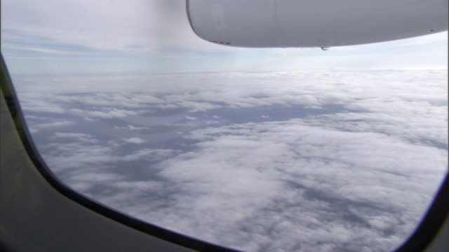 the view from an airplane window reveals the spinning propeller and a layer of clouds below. - propeller stock videos & royalty-free footage