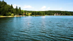 The view of the Lipno lake from fast ship while sailing near to the coastline