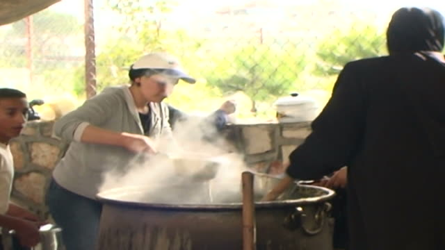 vídeos y material grabado en eventos de stock de the villagers of kfarman gather around cauldrons of hrisseh a traditional lebanese porridge made from wheat and eaten at feasts, in this case the... - ashura