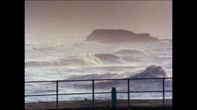 montage the violent sea sends giant waves to strike the english shore where a lighthouse sits / united kingdom - peter greenaway stock videos & royalty-free footage