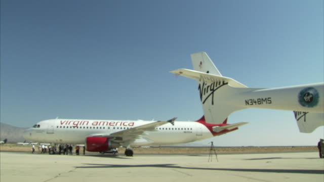 the virgin galactic parks next to a traditional airliner. - logo stock videos & royalty-free footage