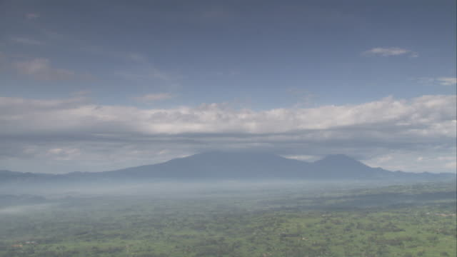 The Virunga Mountain volcanoes rise above a valley. Available in HD.