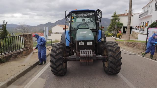 vídeos y material grabado en eventos de stock de the volunteers disinfecting the streets of the town with the tractor. volunteers disinfect the streets of the city during the coronavirus pandemic on... - maquinaria agrícola