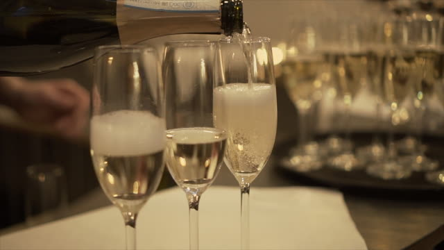 the waiter pours champagne into glasses, close-up. - stock video - champagne stock videos & royalty-free footage