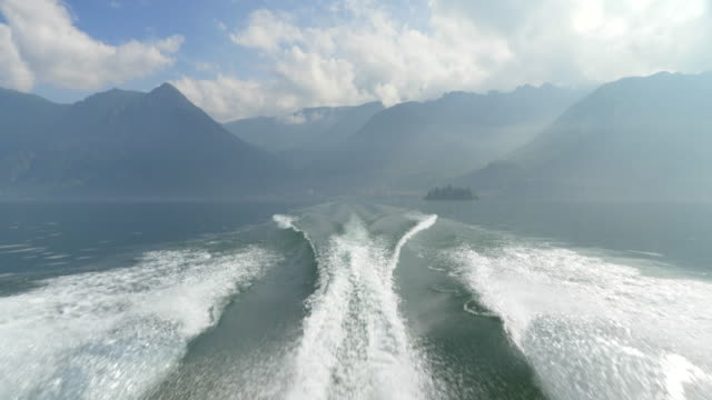 The wake from a classic luxury wooden runabout boat on an Italian lake. - Slow Motion