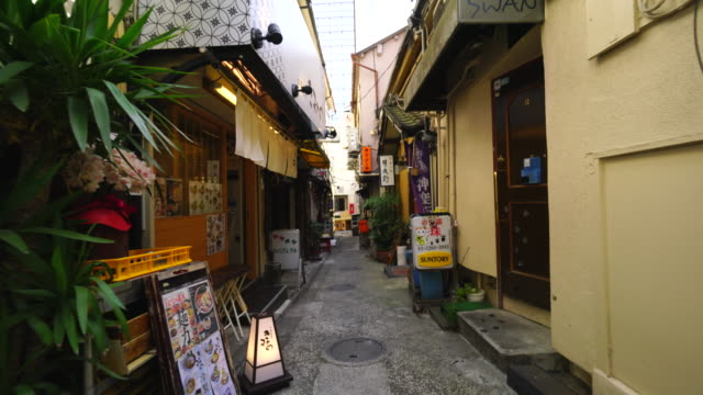 the walking camera going through the narrow alleyway of michikusa yokocho in kagurazaka tokyo.there are many restaurants, bars and shops along the both side of alleyway. - alley stock videos & royalty-free footage