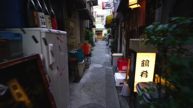 the walking camera going through the narrow alleyway of michikusa yokocho to kagura kouji in kagurazaka tokyo.there are many restaurants, bars and shops along the both side of alleyway. - kagura stock videos & royalty-free footage