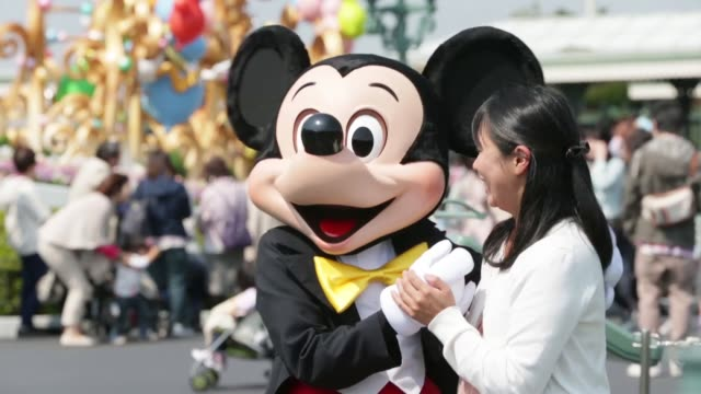 the walt disney co character mickey mouse poses for a photograph with a visitor at tokyo disneyland operated by oriental land co in urayasu city... - land bildbanksvideor och videomaterial från bakom kulisserna