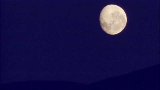 the waning moon shines brightly in an inky night sky. available in hd. - half moon stock videos & royalty-free footage