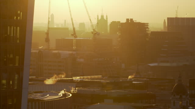 the warm orange glow of sunlight just before sunset over the rooftops of the london skyline - victoria tower stock videos & royalty-free footage