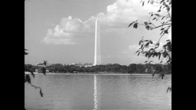 / LS of the Washington Memorial in the background with the Lincoln Memorial Reflecting Pool in the foreground / CU base of memorial and the circle of...