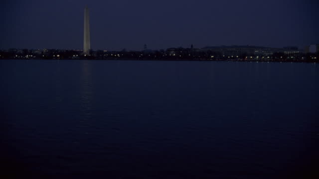 pan the washington monument and jefferson memorial illuminated across tidal basin / washington, district of columbia, united states - jefferson memorial stock videos and b-roll footage