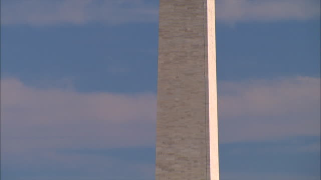 The Washington Monument contrasts against a blue sky.