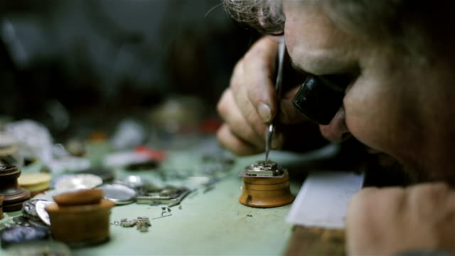vídeos de stock e filmes b-roll de the watchmaker is repairing and maintaining an automatic mechanical watch - fixing and examining pendulum - relógio de pulso