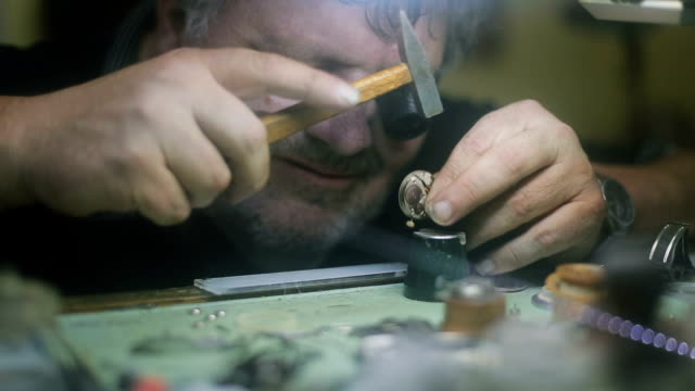 The watchmaker is repairing and maintaining watch - hammering , hard work