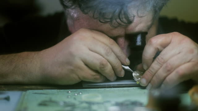 The watchmaker is repairing and maintaining watch