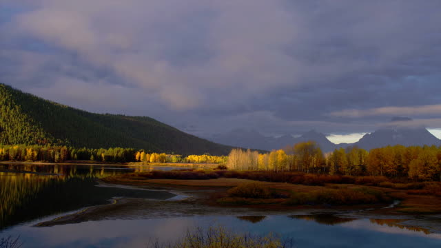 stockvideo's en b-roll-footage met the water in oxbow bend reflects autumn trees and mountains in grand teton national park. - grand teton national park