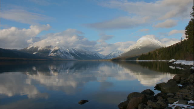 The water of Lake McDonald reflects white clouds moving over snowy mountains in Glacier National Park.