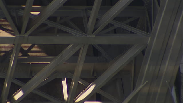 The water of the Seine River reflects off the support beams of the Austerlitz Viaduct. Available in HD.