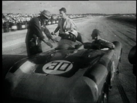 stockvideo's en b-roll-footage met 1957 montage the waving of a checkered flag signifies stirling moss as car race winner / nassau, bahamas - 1957