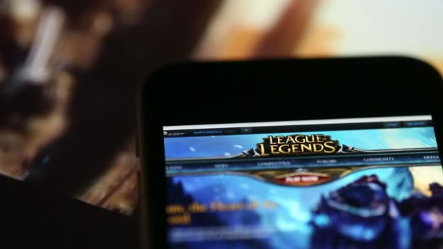 the website for league of legends a video game developed by riot games inc controlled by tencent holdings ltd is displayed on an apple inc iphone 5c... - in buona condizione video stock e b–roll