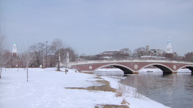 the weeks memorial bridge spans the charles river edged with snow. - charles river stock videos & royalty-free footage