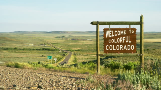 """the """"welcome to colorful colorado"""" state line sign on the colorado/wyoming border at sunset - small town america stock videos & royalty-free footage"""