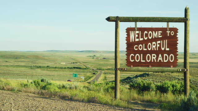 """the """"welcome to colorful colorado"""" state line sign on the colorado/wyoming border at sunset - welcome segnale inglese video stock e b–roll"""