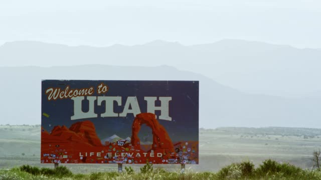 "the ""welcome to utah"" on the utah/colorado border (eastern utah) on interstate 70 with mountains in the background - utah stock videos & royalty-free footage"