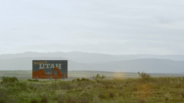 "the ""welcome to utah"" on the utah/colorado border (eastern utah) on interstate 70 with mountains in the background - place sign stock videos & royalty-free footage"