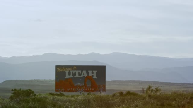 "the ""welcome to utah"" on the utah/colorado border (eastern utah) on interstate 70 with mountains in the background - welcome sign stock videos & royalty-free footage"