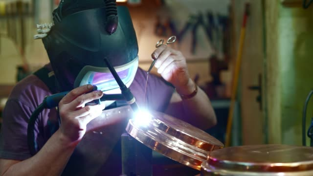 the welder working on the brass details with the electrical welding - health and safety stock videos & royalty-free footage