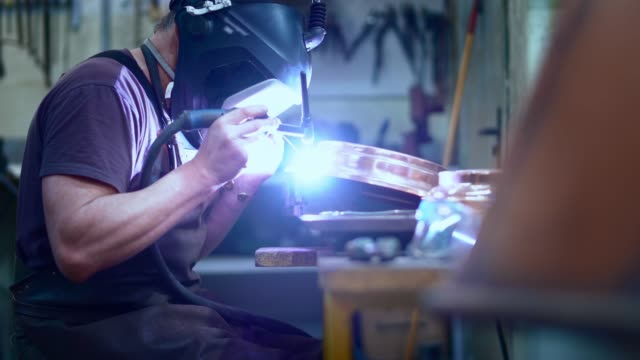 the welder working on the brass details with the electrical welding - copper stock videos & royalty-free footage