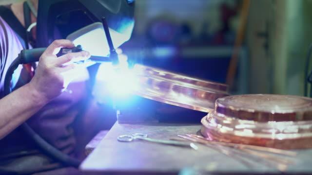 der schweißer arbeitet mit dem elektrischen schweißen an den messingdetails - messing about stock-videos und b-roll-filmmaterial