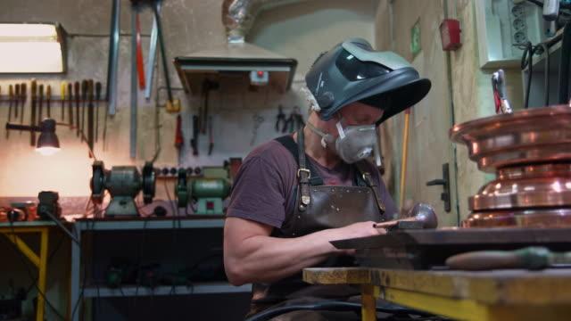 il saldatore che lavora sui dettagli in ottone con la saldatura elettrica - occupazione industriale video stock e b–roll