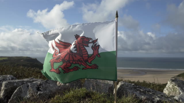 the welsh dragon flag blowing in the wind. - wales stock videos & royalty-free footage