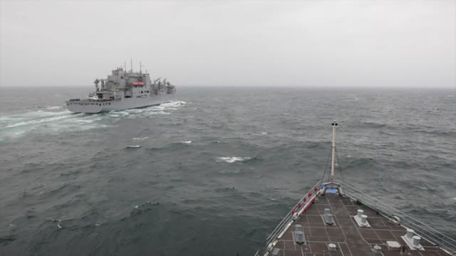 The Whidbey Islandclass amphibious dock landing ship USS Fort McHenry conducts a vertical replenishment with the Henry J Kaiserclass fleet...