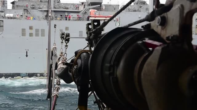 The Whidbey Islandclass amphibious dock landing ship USS Fort McHenry conducts a vertical replenishment with the Lewis and Clarkclass dry cargo ship...