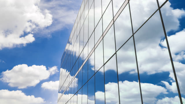 the white clouds are reflected in the windows of the building - specchio video stock e b–roll