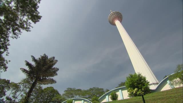 the white exterior of the kuala lumpur tower shines in the sun. - kuala lumpur tower bildbanksvideor och videomaterial från bakom kulisserna