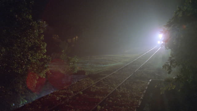the white lights from an oncoming train mix with the orange lights of a railroad crossing. - 1998 stock-videos und b-roll-filmmaterial