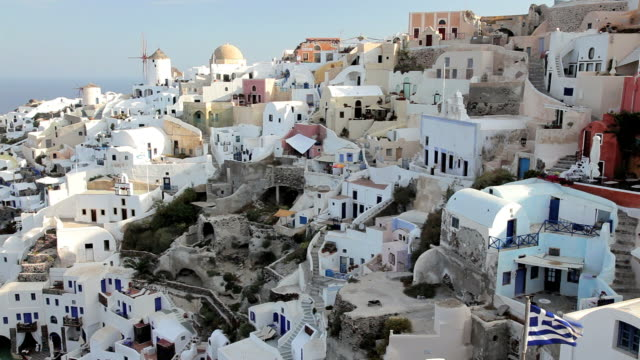 vídeos de stock, filmes e b-roll de the white washed homes in the town of oia with a view overlooking the aegean sea on the island of santorini, greece, europe - oia santorini