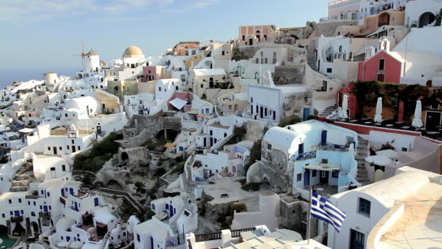 the white washed homes in the town of oia with a view overlooking the aegean sea on the island of santorini, greece, europe - 白しっくい塗点の映像素材/bロール
