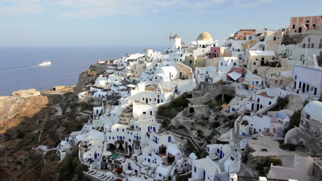 The white washed homes in the town of Oia with a view overlooking the Aegean Sea on the Island of Santorini, Greece, Europe