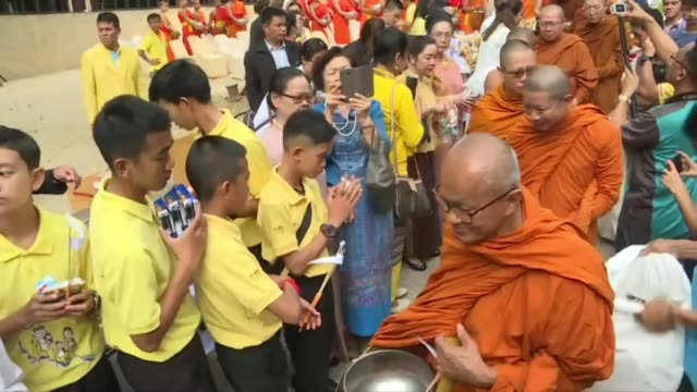 the wild boars football team who became trapped in a cave in northern thailand for 18 days a year ago attend an alms giving ceremony for buddhist... - religious equipment stock-videos und b-roll-filmmaterial